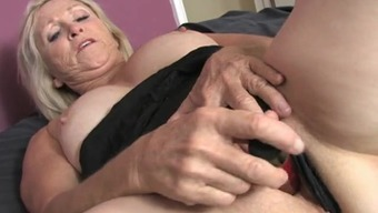 Freckled granny plunges a toy into her moist crimson