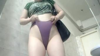Brunette chubby light colored female in green ensemble filmed in the toilet