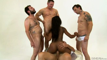 Dirty heated ebony younger slut on her legs nourishing on a bunch of white colored cocks
