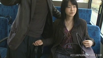 Delicious Japanese MILF gives handjob in that case pussy generously applied in public