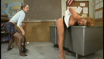 Attractive teenager whips and products her busty instructor inside a college