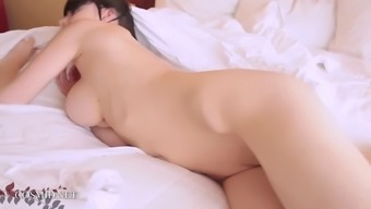 Lovely brunette with large tits rolling in bed totally nude