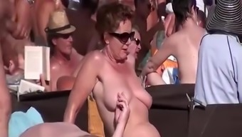 Blowjob in busy nudist seashore